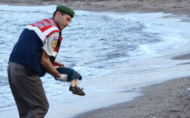GRAPHIC CONTENT  A Turkish police officer carries a migrant child's dead body off the shores in Bodrum, southern Turkey, on September 2, 2015 after a boat carrying refugees sank while reaching the Greek island of Kos. Thousands of refugees and migrants arrived in Athens on September 2, as Greek ministers held talks on the crisis, with Europe struggling to cope with the huge influx fleeing war and repression in the Middle East and Africa. AFP PHOTO / DOGAN NEWS AGENCY  = TURKEY OUT =   TURKEY-GREECE-EUROPE-MIGRANTS TURKEY-GREECE-EUROPE-MIGRANTS