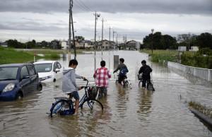 FRA03 KOSHIGAYA (JAPÓN) 10/9/2015 Niños circulan con sus bicicletas por una calle inundada en Koshih¡gaya, en el barrio de Saitama en Tokio, hoy 10 de septiembre de 2015. El tifón Etau causó hoy lluvias récord, graves inundaciones y la evacuación de casi 100.000 personas en el centro y el este de Japón, donde el fenómeno meteorológico también ha dejado al menos un desaparecido y decenas de heridos.EFE/FRANCK ROBICHON