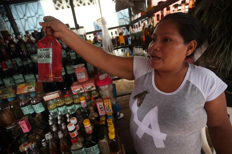ACOMPAÑA CRÓNICA: PERÚ TURISMO LIM13. IQUITOS (PERÚ), 11/12/2015.- Fotografía del 6 de diciembre de 2015 de una vendedora ofreciendo un licor afrodisiaco a base de camu camu, fruta amazónica con alto nivel de vitamina C, en el mercado de Belén, en Iquitos (Perú). El exótico mercado de Belén, en Iquitos, la ciudad más grande del mundo en plena Amazonía peruana a la que solo se puede llegar en avión o en barco, es un espectáculo único en el que se encuentra gran variedad de pescados, frutas de la selva y todo tipo de plantas medicinales y licores afrodisíacos. Situado junto al barrio flotante de Belén, conocido como la Venecia amazónica aunque en lugar de palacios solo hay polvorientas casas donde sobreviven los más pobres, hasta el mercado llegan a diario gigantescos pescados como el paiche, y otros como el zúngaro, la doncella o la gamitana. EFE/Ernesto Arias