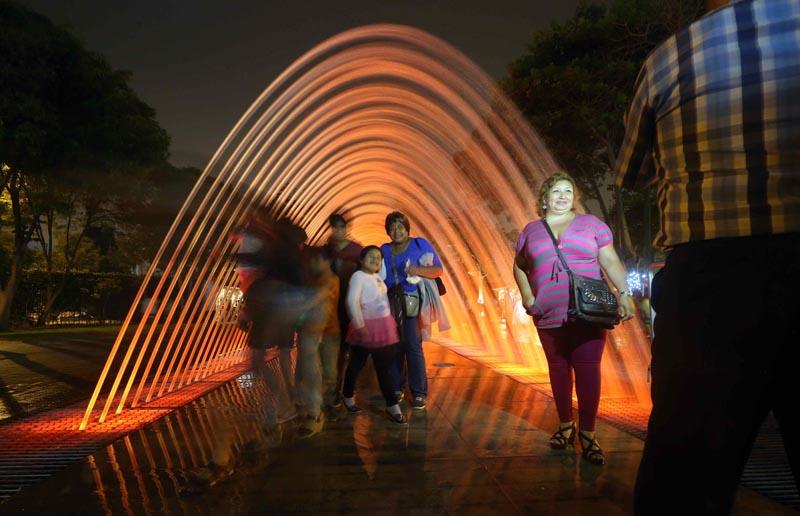 LIM01 LIMA (PERÚ), 15/01/2016.- Asistentes caminan por el interior del túnel de agua de una de las fuentes remodeladas del Parque de la Reserva en Lima (Perú) hoy, viernes 15 de enero de 2016. El parque de la Reserva de Lima estrenó hoy las remodeladas fuentes de su circuito mágico del agua , que ahora cuenta con la pantalla de agua mas grande del mundo , en un parque público en la que se proyecta un especáculo audiovisual sobre sus 95 metros de largo, según la municipalidad de Lima. EFE/Ernesto Arias