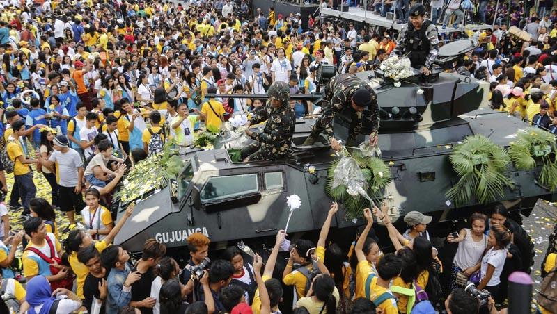 FRM11 QUEZON (FILIPINAS) 25/02/2016.- La multitud entrega flores a soldados que marchan durante el desfile celebrado con motivo del trigésimo aniversario de la Revolución del Poder del Pueblo en Quezon al este de Manila (Filipinas) hoy, 25 de febrero de 2016. Filipinas recuerda así la caída de la dictadura de Ferdinand Marcos en 1986. EFE/Mark R. Cristino