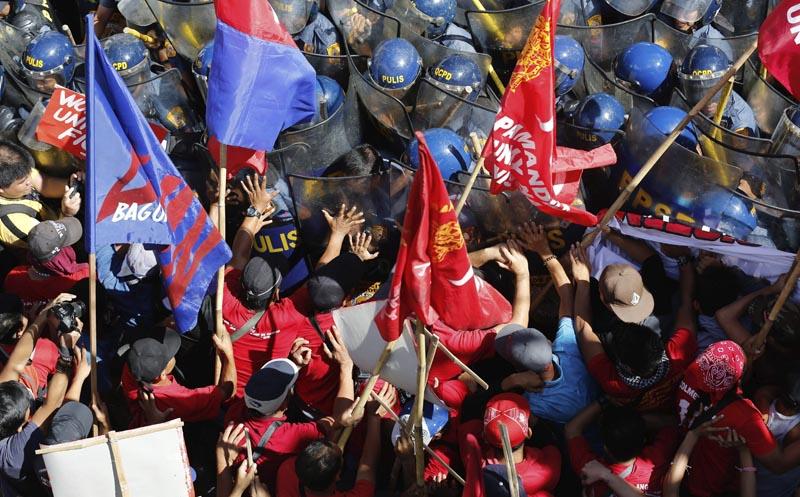 FRM17 QUEZON (FILIPINAS) 25/02/2016.- Policías antidisturbios y manifestantes se enfrentan durante una protesta cleebrada durante el trigésimo aniversario de la Revolución del Poder del Pueblo en Quezon al este de Manila (Filipinas) hoy, 25 de febrero de 2016. Filipinas recuerda así la caída de la dictadura de Ferdinand Marcos en 1986. EFE/Mark R. Cristino