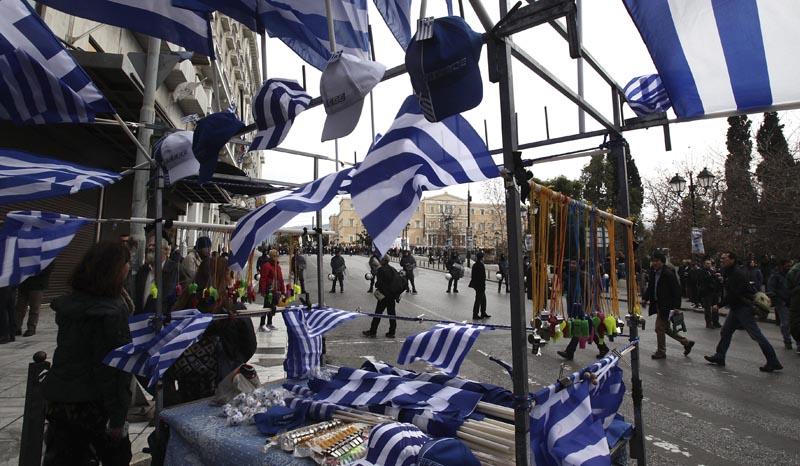SIM24 ATENAS (GRECIA) 04/02/2016.- Un vendedor ambulante vende banderas griegas durante una manifestación en Atenas (Grecia) hoy, 4 de febrero de 2016. Grecia vivió hoy la primera huelga general del año en contra de la reforma de las pensiones que dejó una imagen totalmente diferente a la de convocatorias anteriores, pues el pequeño comercio, los taxistas y el transporte paralizaron la actividad en la mayoría de ciudades del país. EFE/Simela Pantzartzi