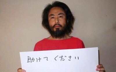 """CORRECTION - This undated picture provided by Japan's Jiji Press news agency, taken at an undisclosed location, on May 30, 2016 shows Japanese freelance journalist Jumpei Yasuda holding a piece of paper with a handwritten message in Japanese.  The fresh photo, which received widespread coverage in Japanese media on May 30, 2016, shows Yasuda, who has been missing for almost a year, wearing an orange shirt, his hair and beard grown long.   / AFP PHOTO / JIJI PRESS / JIJI PRESS / Japan OUT / """"The erroneous mention[s] appearing in the metadata of this photo by JIJI PRESS has been modified in AFP systems in the following manner: corrects first name spelling [Jumpei] instead of [Junpei]. Please immediately remove the erroneous mention[s] from all your online services and delete it (them) from your servers. If you have been authorized by AFP to distribute it (them) to third parties, please ensure that the same actions are carried out by them. Failure to promptly comply with these instructions will entail liability on your part for any continued or post notification usage. Therefore we thank you very much for all your attention and prompt action. We are sorry for the inconvenience this notification may cause and remain at your disposal for any further information you may require."""""""