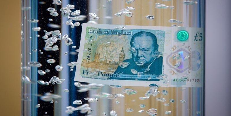 SIM01 WOODSTOCK (REINO UNIDO) 02/06/2016.- Vista general del nuevo billete de cinco libras esterlinas sumergido en un recipiente con agua durante su presentación en el palacio de Blenheim en Oxfordshire, Reino Unido hoy, 2 de junio de 2016. El Banco de Inglaterra desveló hoy el diseño de su nuevo billete de cinco libras esterlinas (6,45 euros), el primero fabricado con plástico en el Reino Unido, que entrará en circulación en próximo 13 de septiembre. EFE/Simon Dawson /POOL