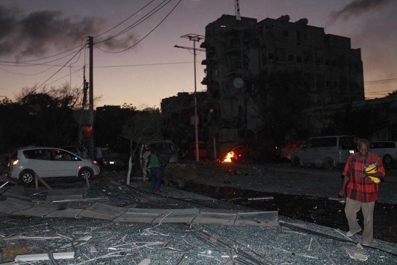 DAI02 MOGADISCIO (SOMALIA), 01/06/2016.- Varias personas en el lugar del atentado tras el ataque con coche bomba contra un céntrico hotel de la capital en Mogasdiscio, Somalia, hoy 1 de junio de 2016. Al menos 7 personas han muerto y 17 han resultado heridas en el popular Hotel Ambassador, donde se registró una gran explosión producida por un coche bomba, antes de que un grupo de cinco yihadistas irrumpieran en sus instalaciones. EFE/Said Yusuf Warsame
