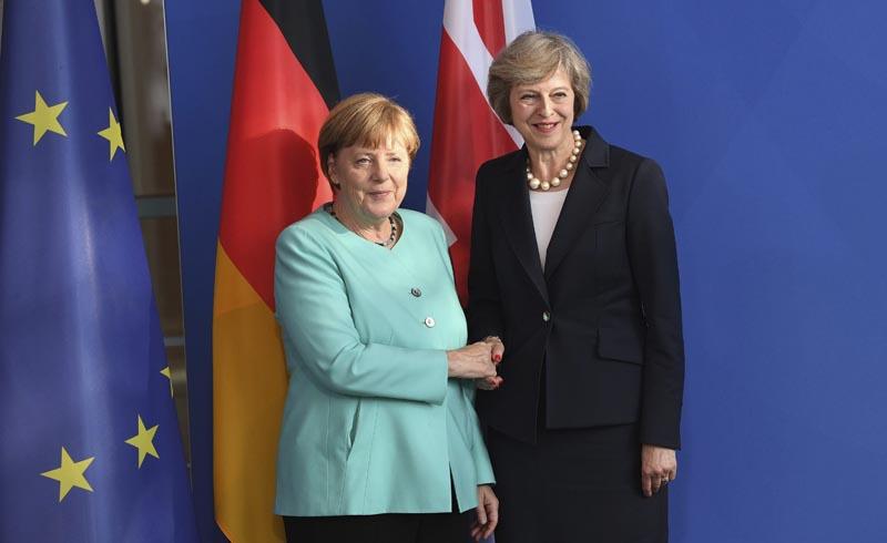 """BER101 BERLÍN (ALEMANIA), 20/07/2016.- La canciller alemana, Angela Merkel (i), estrecha la mano de la primera ministra británica, Theresa May, durante una rueda de prensa conjunta en la Cancillería de Berlín, Alemania, hoy, 20 de julio de 2016. May realiza su primer viaje al extranjero desde que asumió el cargo tras el triunfo del """"brexit"""" en el referéndum celebrado en el Reino Unido. EFE/SOEREN STACHE"""