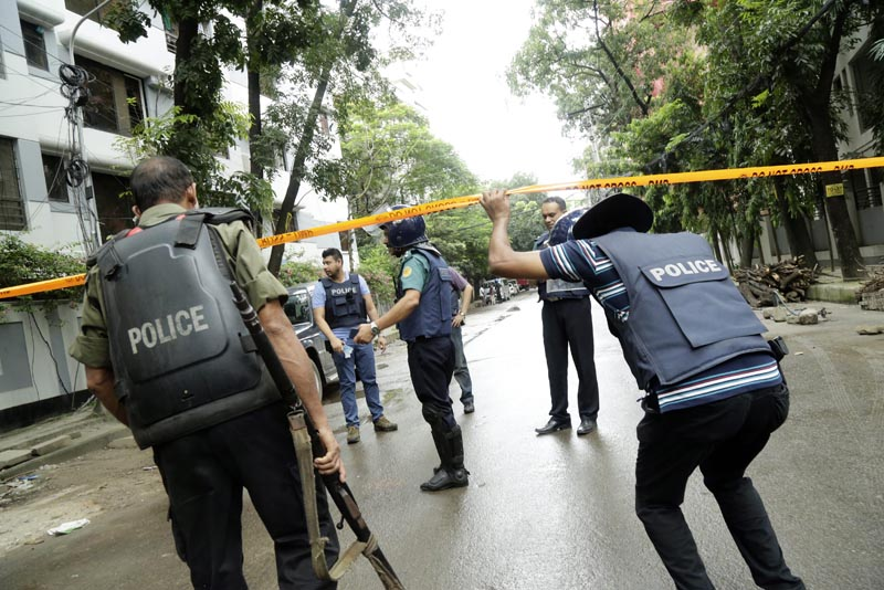 AAA12. Dhaka (Bangladesh), 02/07/2016.- Policemen behind tape to resrict media and others in the streets close to the Holey Artisan Bakery in Dhaka, Bangladesh 02 July 2016. Six gunmen have been shot and killed during an operation to end a hostage situation by military commandos, while two policemen were killed by the gunmen earlier and more than 20 people were injured. EFE/EPA/STRINGER
