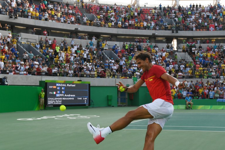Spain's Rafael Nadal kicks a signed tennis ball into the crowd after winning his men's second round singles tennis match against Italy's Andreas Seppi at the Olympic Tennis Centre of the Rio 2016 Olympic Games in Rio de Janeiro on August 9, 2016. / AFP PHOTO / Luis Acosta