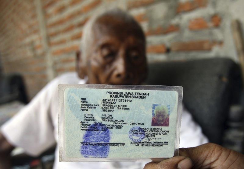 """LUT07 SRAGEN (INDONESIA) 29/08/2016.- Sodimejo alias """"Mbath Gotho"""", de 145 años de edad, muestra su carné de identidad en el que aparece su fecha de nacimiento, 31 de diciembre de 1870, durante una entrevista en su casa en Sragen (Indonesia) hoy, 29 de agosto de 2016. EFE/Ali Lutfi"""
