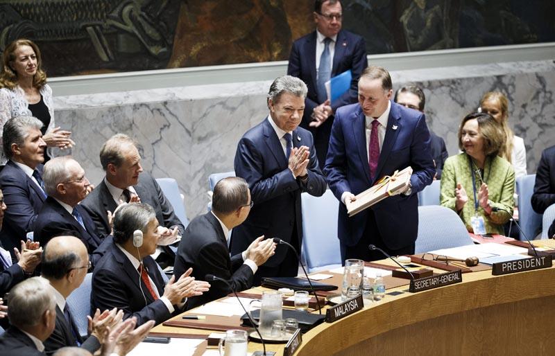 AGX12 NUEVA YORK (ESTADOS UNIDOS) 21/09/2016.- El presidente de Colombia, Juan Manuel Santos (c-i), entrega una copia del reciente acuerdo de paz entre Colombia y las FARC al primer ministro de Nueva Zelanda, John Key (c-d), cuyo país preside este mes ese órgano de decisiones de la ONU, durante una reunión sobre el acuerdo de paz celebrada en el marco del debate del 71 periodo de sesiones de la Asamblea General de Naciones Unidas, en la sede del a ONU en Nueva York, Estados Unidos, hoy, 21 de septiembre de 2016. EFE/Justine Lane