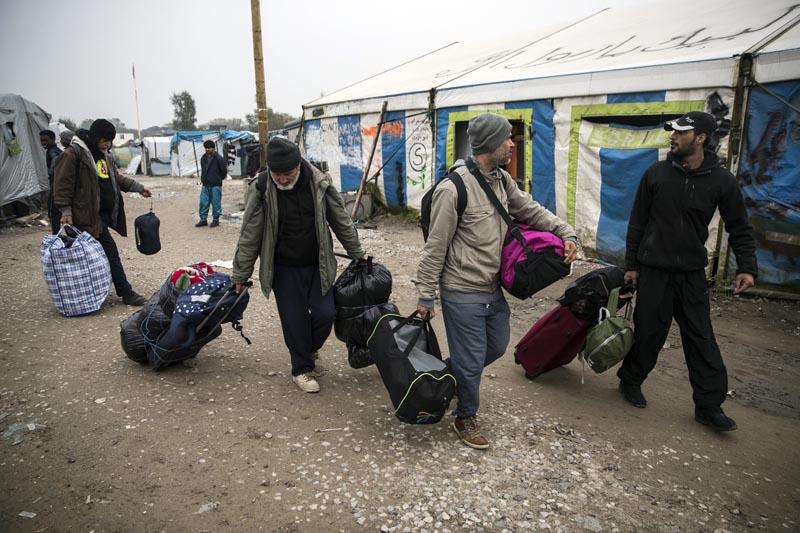 """TIB01 CALAIS (FRANCIA), 24/10/2016.- Varias personas cargan con sus pertenencias durante la evacuación del campo de inmigrantes de Calais, el mayor de Francia hoy 24 de octubre de 2016. El ministro francés del Interior, Bernard Cazeneuve, subrayó hoy el carácter humanitario del desmantelamiento del campamento de inmigrantes conocido como la """"jungla"""" de Calais, y aseguró que se está llevando a cabo de forma tranquila y controlada. EFE/Etienne Laurent"""