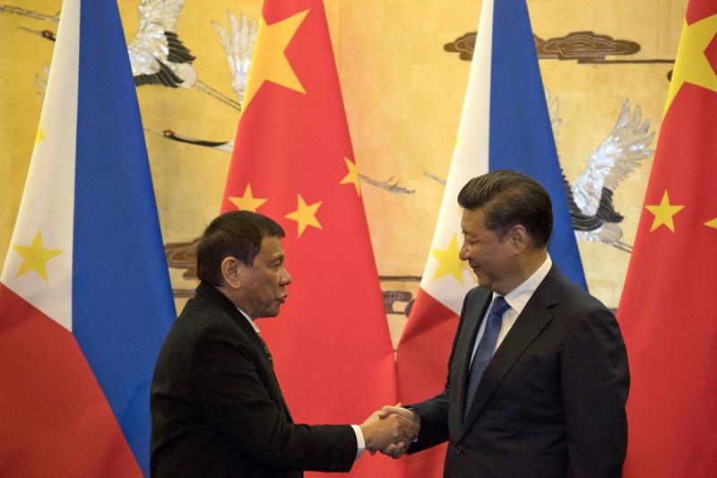 """XHG12010 PEKÍN (CHINA) 20/10/2016.- El presidente chino, Xi Jinping (dcha), estrecha la mano a su homólogo filipino, Rodrigo Duterte, tras participar en una ceremonia de firma de acuerdos en Pekín (China) hoy, 20 de octubre de 2016. Duterte fue recibido hoy con honores en Pekín por su homólogo chino, Xi Jinping, quien calificó la visita de """"hito"""" en las relaciones chino-filipinas, marcadas desde hace años por disputas territoriales en el mar de China Meridional. EFE/Ng Han Guan/Pool"""
