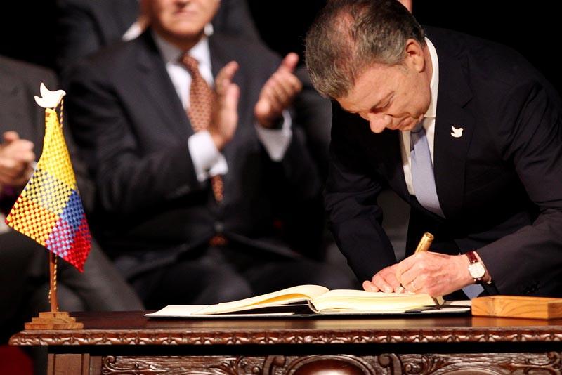 """BOG107. BOGOTÁ (COLOMBIA), 24/11/2016.- El presidente de Colombia Juan Manuel Santos firma el nuevo acuerdo de paz para terminar 52 años de conflicto armado interno hoy, jueves 24 de noviembre de 2016, en Bogotá (Colombia). Santos y el jefe máximo de las FARC Rodrigo Londoño Echeverry """"Timochenko"""" firmaron el acuerdo, que complementa el original del pasado 26 de septiembre en Cartagena de Indias, a las 11.30 hora local (16.30 GMT) en el Teatro Colón de Bogotá. Primero lo hizo el jefe guerrillero y luego el jefe de Estado, quienes utilizaron, al igual que en el primer acuerdo, un """"balígrafo"""", bolígrafo fabricado con un casquillo de bala de fusil, que simboliza el tránsito de Colombia de la guerra a la paz. EFE/MAURICIO DUENAS CASTAÑEDA"""