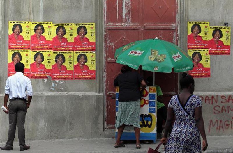 HAI08 PUERTO PRÍNCIPE (HAITÍ) 18/11/16.- Un hombre observa los carteles de una de las candidatas, hoy viernes 18 de noviembre de 2016, en la ciudad de Puerto Príncipe. El Gobierno de Haití anunció hoy el cierre de su frontera mañana y el domingo por la celebración este último día de las elecciones generales, medida que según el Ministerio del Interior haitiana asegura más control durante la jornada electoral. EFE/Alejandro Ernesto