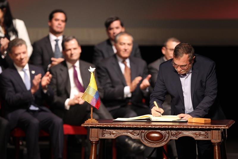 """BOG102. BOGOTÁ (COLOMBIA), 24/11/2016.- El jefe máximo de las FARC Rodrigo Londoño Echeverry (d) firma el nuevo acuerdo de paz para terminar 52 años de conflicto armado interno hoy, jueves 24 de noviembre de 2016, en Bogotá (Colombia). El presidente de Colombia Juan Manuel Santos y """"Timochenko"""" firmaron el acuerdo, que complementa el original del pasado 26 de septiembre en Cartagena de Indias, a las 11.30 hora local (16.30 GMT) en el Teatro Colón de Bogotá. Primero lo hizo el jefe guerrillero y luego el jefe de Estado, quienes utilizaron, al igual que en el primer acuerdo, un """"balígrafo"""", bolígrafo fabricado con un casquillo de bala de fusil, que simboliza el tránsito de Colombia de la guerra a la paz. EFE/MAURICIO DUENAS CASTAÑEDA"""