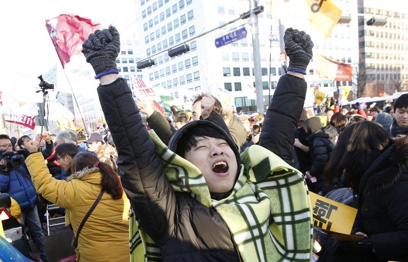 """SE50 SEÚL (COREA DEL SUR) 09/12/2016.- Una multitud celebra la aprobación de la destitución de la presidenta durante una protesta ante la Asamblea Nacional en Seúl (Corea del Sur) hoy, 9 de diciembre de 2016. El Parlamento de Corea del Sur aprobó hoy con más de dos tercios de los votos la destitución de la presidenta Park Geun-hye, implicada en el grave escándalo de la """"Rasputina coreana"""". EFE/Jeon Heon-Kyun"""