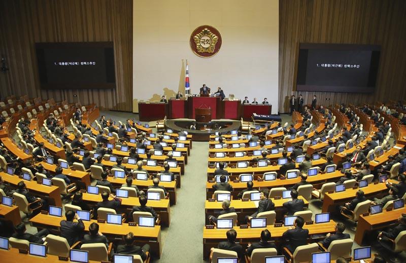 """SE025 SEÚL (COREA DEL SUR) 09/12/2016.- Diputados esperan el resultado de la votación de la destitución de la presidenta surcoreana, Park Geun-hye, en la Asamblea Nacional en Seúl (Corea del Sur) hoy, 9 de diciembre de 2016. El Parlamento de Corea del Sur aprobó hoy con más de dos tercios de los votos la destitución de la presidenta Park Geun-hye, implicada en el grave escándalo de la """"Rasputina coreana"""". El """"sí"""" al proceso de destitución ganó con 234 papeletas a favor, 56 en contra, 7 votos nulos y 2 abstenciones poco más de una hora después de comenzar la sesión en la que votaron 299 de los 300 representantes de la cámara baja. La pelota cae ahora en el tejado del Tribunal Constitucional, donde al menos seis de sus nueve jueces deben dar el visto bueno a la decisión del parlamento, en un proceso que llevaría 180 días como máximo. EFE/Stringer PROHIBIDO SU USO EN COREA DEL SUR"""