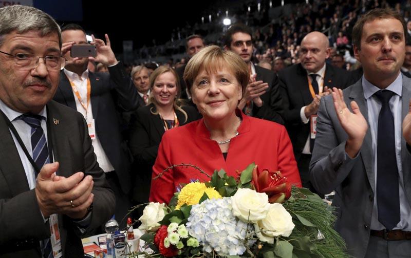 ESS63 ESSEN (ALEMANIA), 06/12/2016.- La canciller alemana, Angela Merkel (c), tras ser reelegida presidenta de la Unión Cristianodemócrata (CDU) con un 89,5 % de los votos, en el congreso federal que celebra la formación en Essen, Alemania, hoy, 6 de diciembre de 2016. Merkel obtuvo este resultado, frente al 96,7 % logrado dos años atrás, y fue ratificada así como líder del partido, dos semanas después de haber anunciado que optará a un cuarto mandato como canciller en los comicios previstos para dentro de diez meses. EFE/MICHAEL KAPPELER