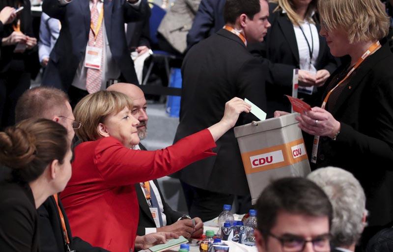 ESS63 ESSEN (ALEMANIA), 06/12/2016.- La canciller alemana, Angela Merkel (c), emite su voto durante el congreso federal de la Unión Cristianodemócrata (CDU), en Essen, Alemania, hoy, 6 de diciembre de 2016. Merkel advirtió hoy que no todos los refugiados llegados desde el año pasado al país podrán permanecer en Alemania, pero garantizó que se evaluará cada caso antes de adoptar una decisión al respecto. EFE/MICHAEL KAPPELER