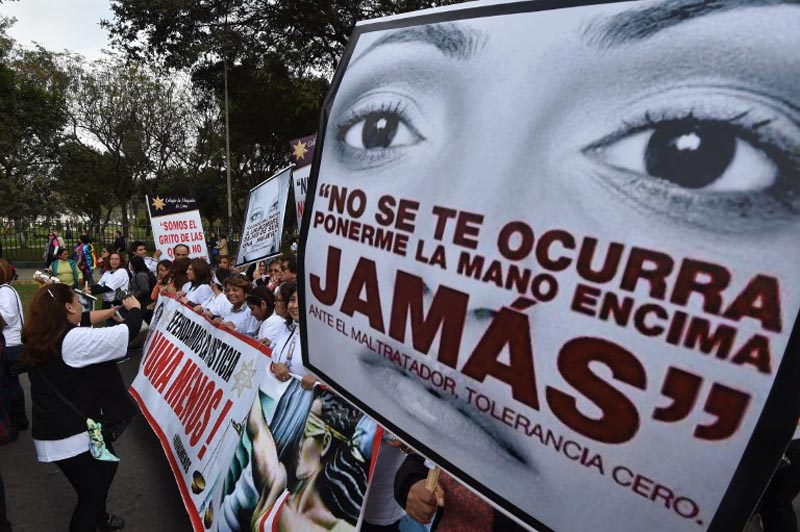 """Thousands of demonstrators participate in the """"Ni una menos"""" (Not One Less) march through the center of Lima to the palace of justice holding banners and posters condemning gender violence and femicide - gender-based killings - on August 13, 2016.  / AFP PHOTO / CRIS BOURONCLE"""